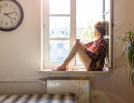 kvinna tittar ut genom fönstret. Har pandemin gjort att vi har fått en antydan till social fobi
